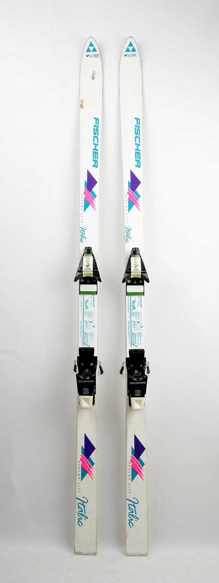Alpinski laga av glasfiber, såle av plast med stålkantar. Kvit overflate, med lilla, grøn og rosa dekor/skrift. Det  sit på bindingar av type Salomon.