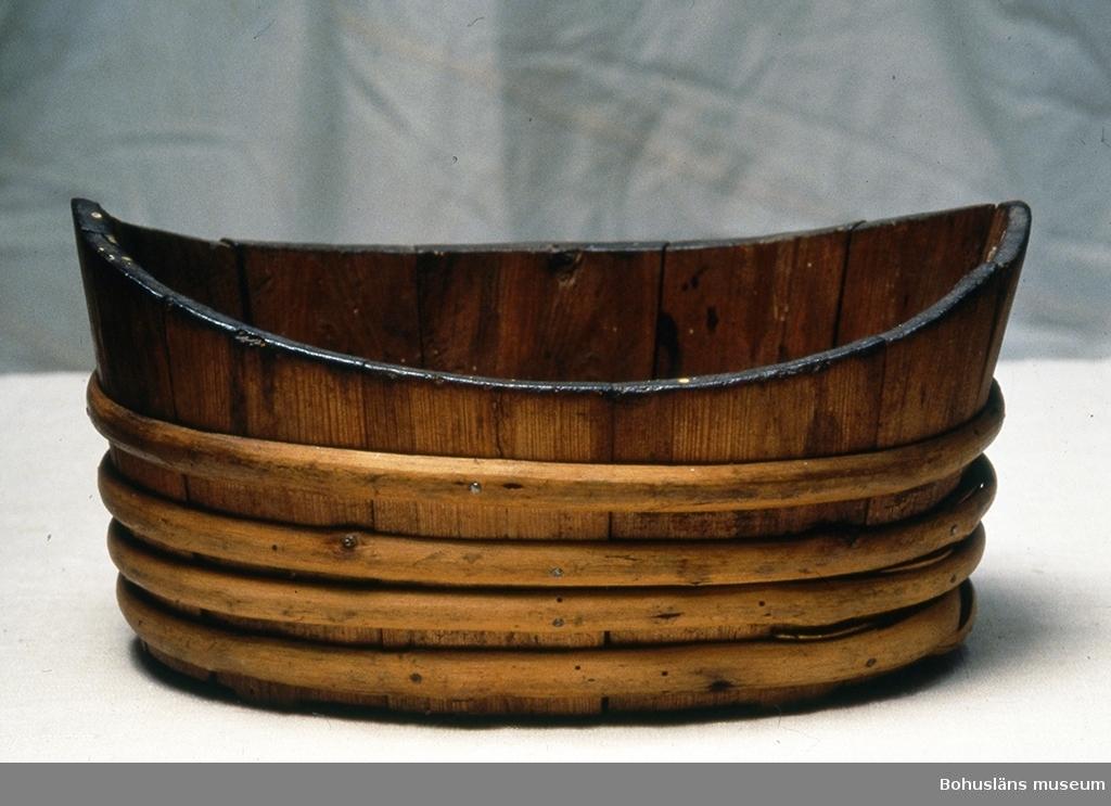 """Ovalt, något """"båtformat"""" laggkärl med fyra tvärgående slåar av pil? för att hålla ihop konstruktionen. Fastspikade sekundärt. Fyra av stavarna har små utsågade fötter nertill. En av stavarna är defekt upp- och nertill.  Litt.; Keyland, Nils, Svensk Allmogekost II, AB SVENSKA TEKNOLOGFÖRENINGENS FÖRLAG, STOCKHOLM, 1919, sid. 12-26. Se bild i Lychou, Kerstin, Hemslöjd & Folkkonst i Bohuslän, Warne förlag AB, Partille 1996, sid. 91.  Ur handskrivna katalogen 1957-1958: Avlångt träkärl Ovalt laggkärl. Bottenmått 24,2 x 16,2. H: 13,5. Omålat. Något skadat. Bohuslän"""