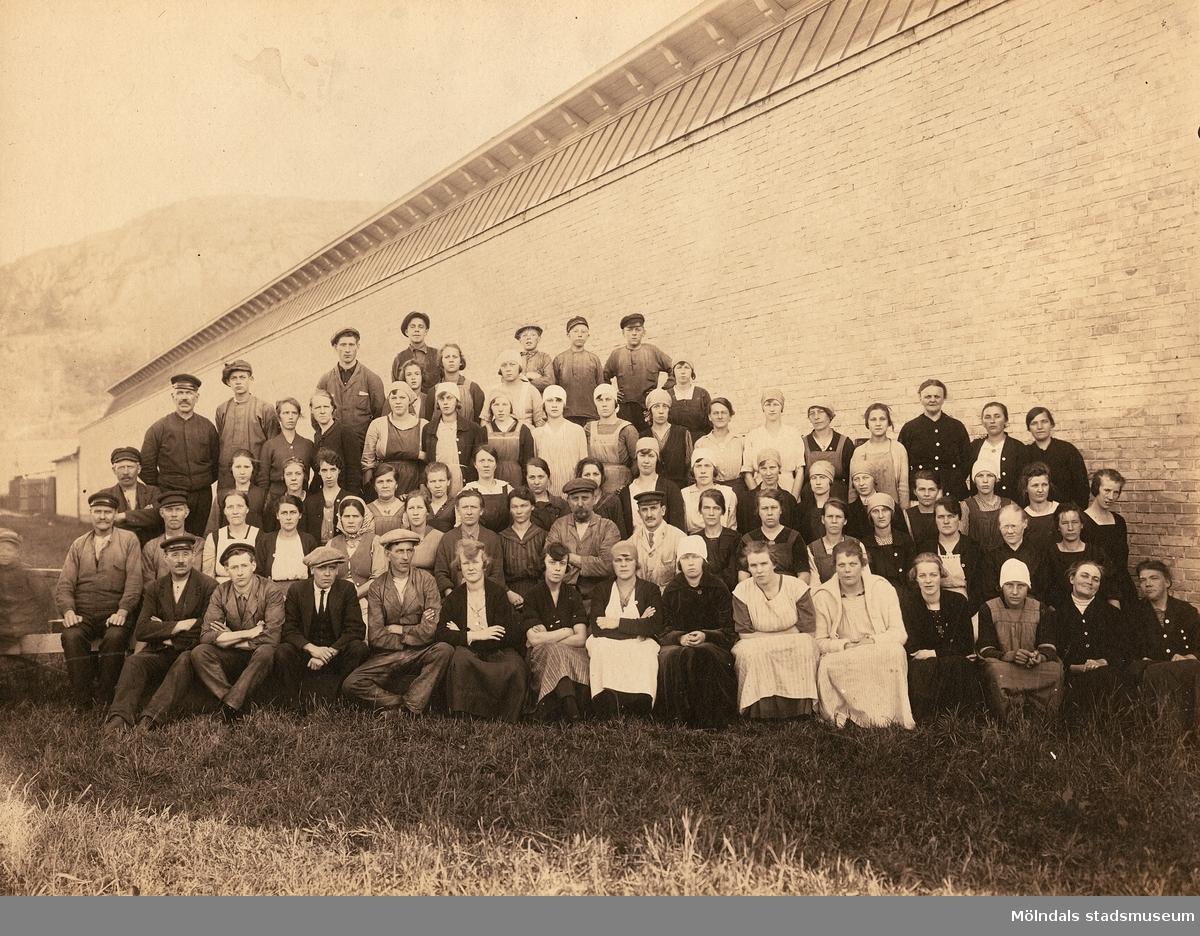 Manliga och kvinnliga spinneriarbetare står uppställda utanför Lana Kamgarnsspinneri i Krokslätt, cirka 1925. På fjärde raden, nionde person från höger (iklädd sjalett och förkläde), står Villy Ljungberg (1905-1982) som var faster till givarens mor. I bakgrunden skymtar Rallarberget.