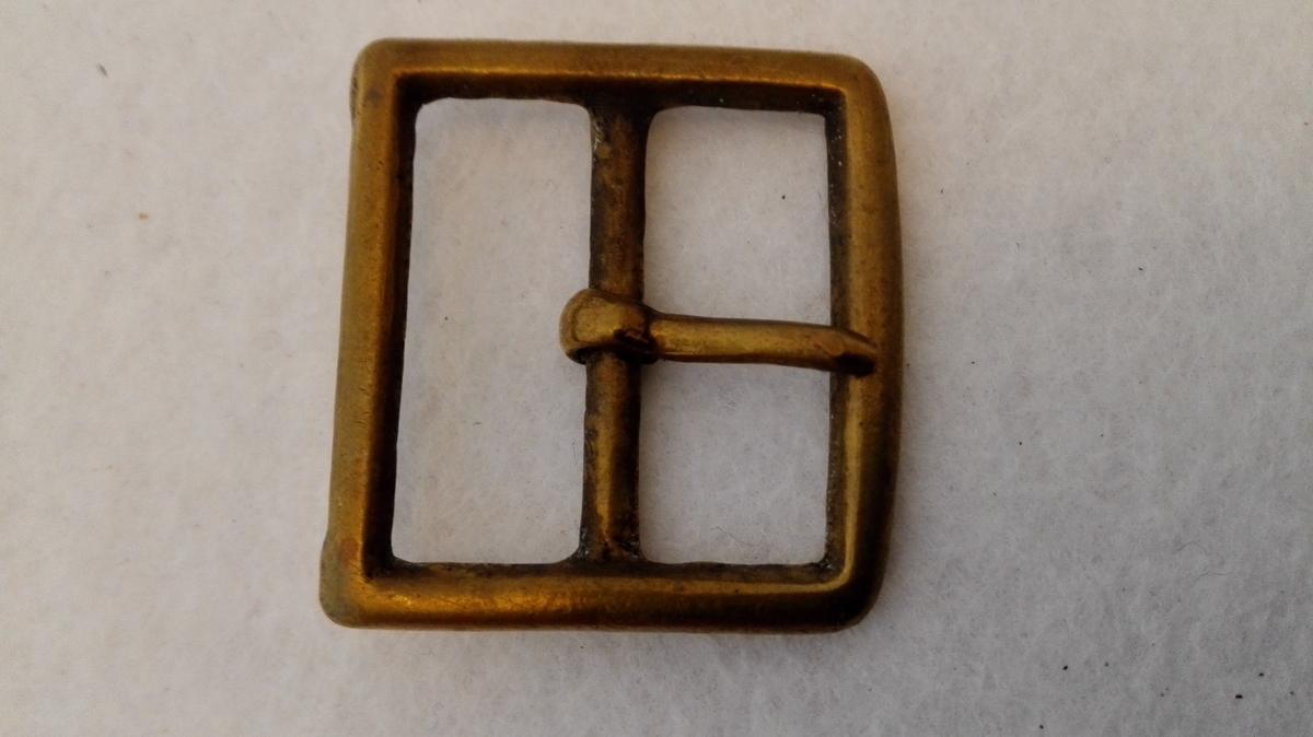 Form: Avlang og firkanta. 1 messingspænde.  Avlang firkantet spænde av messing, messing tand. Den ene side noget avrundet.  Kjöpt av landhandler Theodor Lindström, Lærdal.