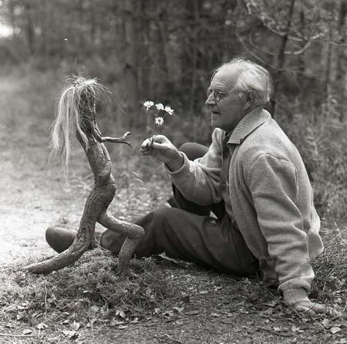 En man räcker fram blommor till ett trätroll, 1958.