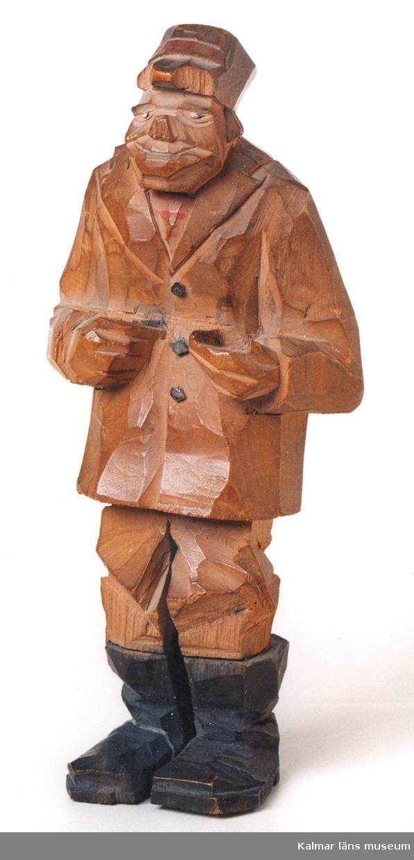 KLM 39255:2. Skulptur, av trä. Gubbe med svarta stövlar och svarta rockknappar. På huvudet kaskliknande skärmmössa, skärmen defekt. I vänster hand troligen suttit mindre föremål, nu förkommit. Osignerad.