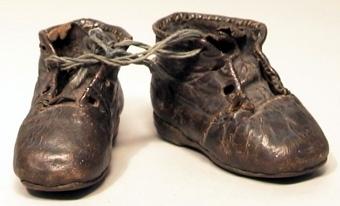 Ett par mörkbruna barnskor med plös. Fyra par hål för snörning mitt fram, pliggad lädersula och sydd läderklack.