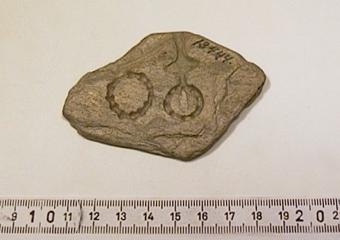 Gjutform av ljusgrå skiffer för fyra runda maljor eller knappar. Fördjupningarna består i huvudsak av punkter.