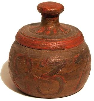Rund, svarvad ask av trä med trycklock försedd med en hög knopp. På lockets insida finns fem runda urtagningar. Asken är målad i gulbrunt med ornering i rött och grönt.