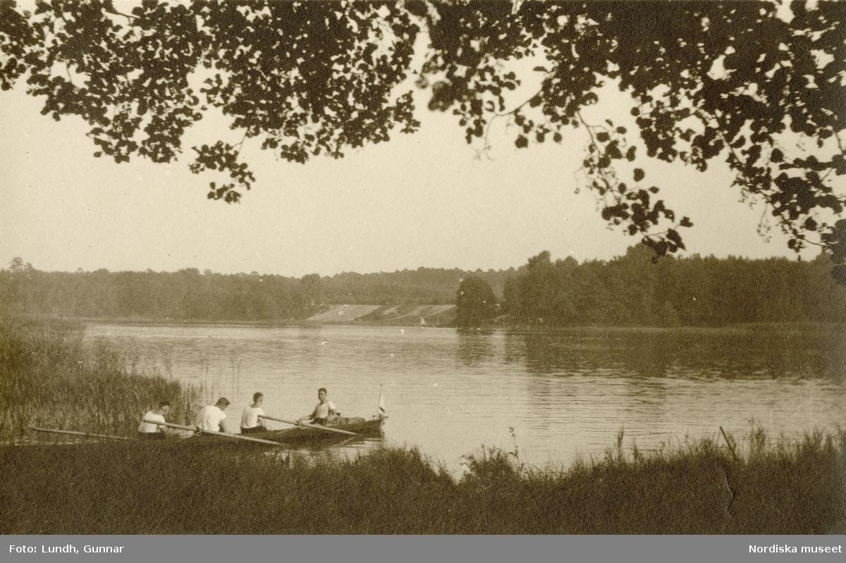 Tyskland. Fyra unga män i en roddbåt i strandkanten vid en sjö.