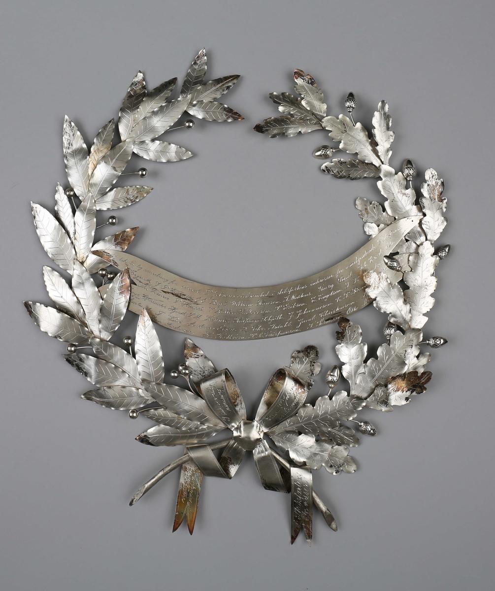 Bårekrans. Krans nedlagt på konsul Peder Jebsen´s båre 1892. Kransen er utført som eikeblader med nøtter, samt sløyfe.