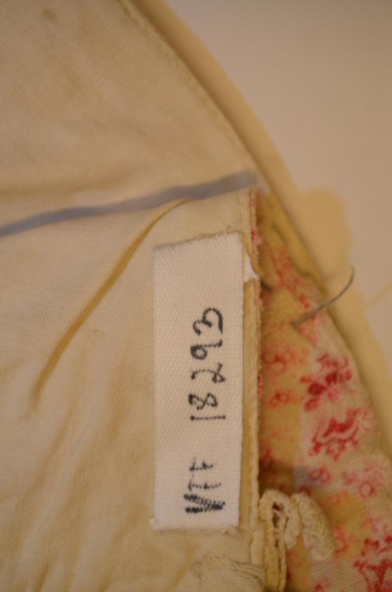 Barnelue i småblomstra trykt bomullstøy i kvit og raudrosa.  Fóra med kvit bomull. I framkant pipefolda blondekant. Maskinsydd.