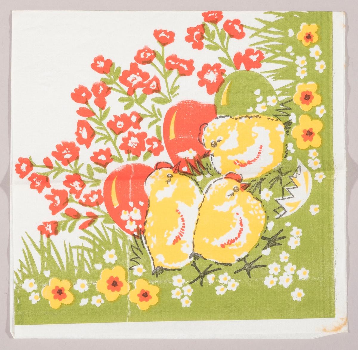Tre kyllinger i en blomstereng med kulørte påskeegg og et skall fra et egg. Grønt gress med røde, hvite og gule blomster.