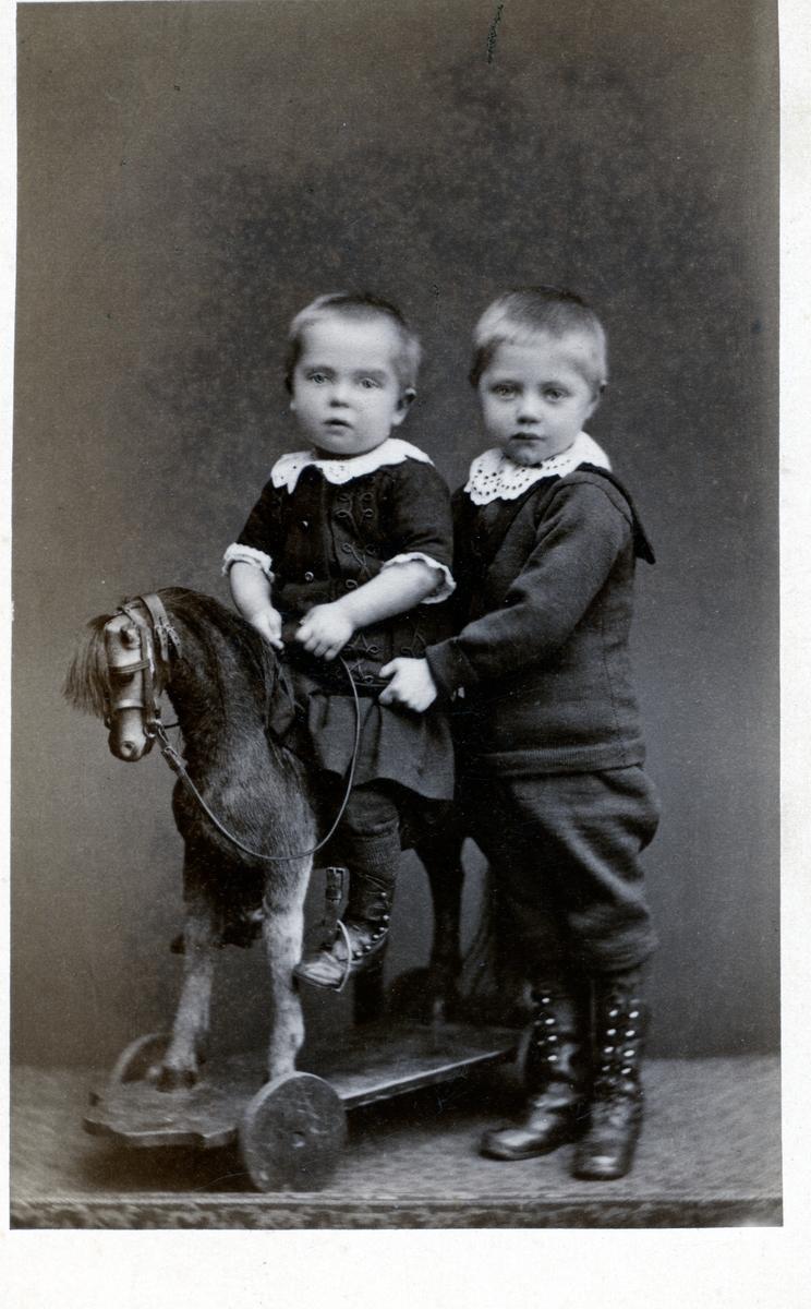 Portrett av to ungar. Den eine sit på ein gyngehest medan den andre står ved sia av.