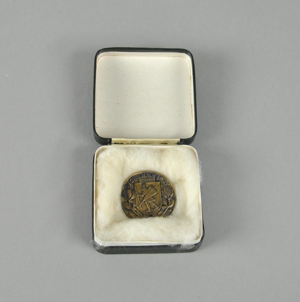 Rund medalje av bronse, med Lillehammer byvåpen i midten med laubærkrans rundt kanten. Tekst på baksiden.