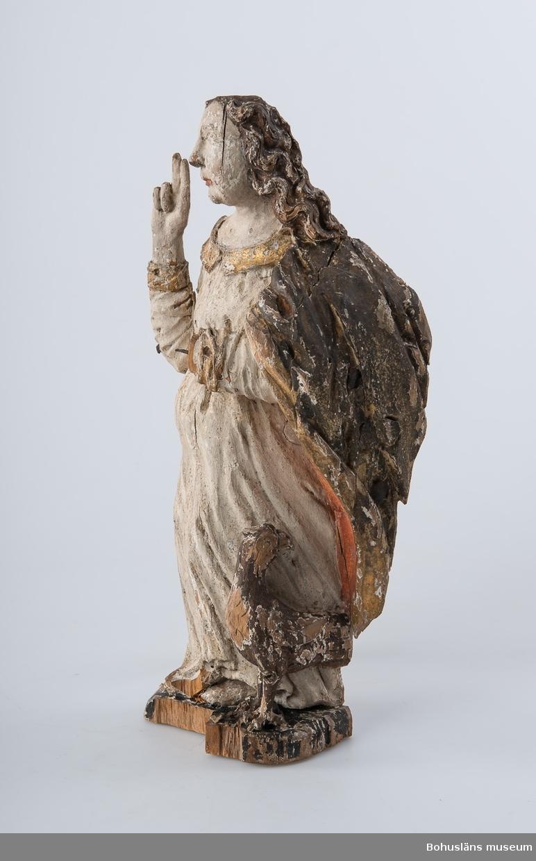Skulptur, apostelbild från 1600-talet som tillhör altartavla UM000393. Krederat trä med mager oljefärg och oljeförgyllning. Förgyllningen uppvisar båda bladguld, slagmetall och/eller silver.  Ur handskrivna katalogen 1957-1958: Apostelbild, Lane Ryr  H. 40 cm; Kristus, höger hand höjd t. välsignande åtbörd, vänster bär ett klot; färgen delvis flagn; sprickor. Krederat trä med mager oljefärg och oljeförgyllning. Förgyllningen uppvisar båda bladguld, slagmetall och/eller silver. Lappkatalog: 13  Se foto på föremålet i Uddevalla museums kyrkliga utställning 1920, UMFA54467:0422.  Ytterligare en kyrklig skulptur är märkt med inventarienummer UM394, aposteln Johannes med välsignelsegest och en örn, manteln är har rödmålad insida. Denna skulptur återfinns emellertid inte på äldre bilder av altartavla UM000393, den äldsta fotot UMFA916 samt ett yngre fotografi, UMFA917 som är taget i kyrkliga utställningen av Maria Lundbäck, och alltså inte kan vara senare än år 1927.  Ur Nationalencyklopedin, NE.se:  Apostel I konsten framställs apostlarna alltid barfota samt klädda i tunika och mantel. De bär oftast en bok samt sitt individuella attribut, i allmänhet respektive martyrredskap (Petrus bär dock himmelrikets nycklar).