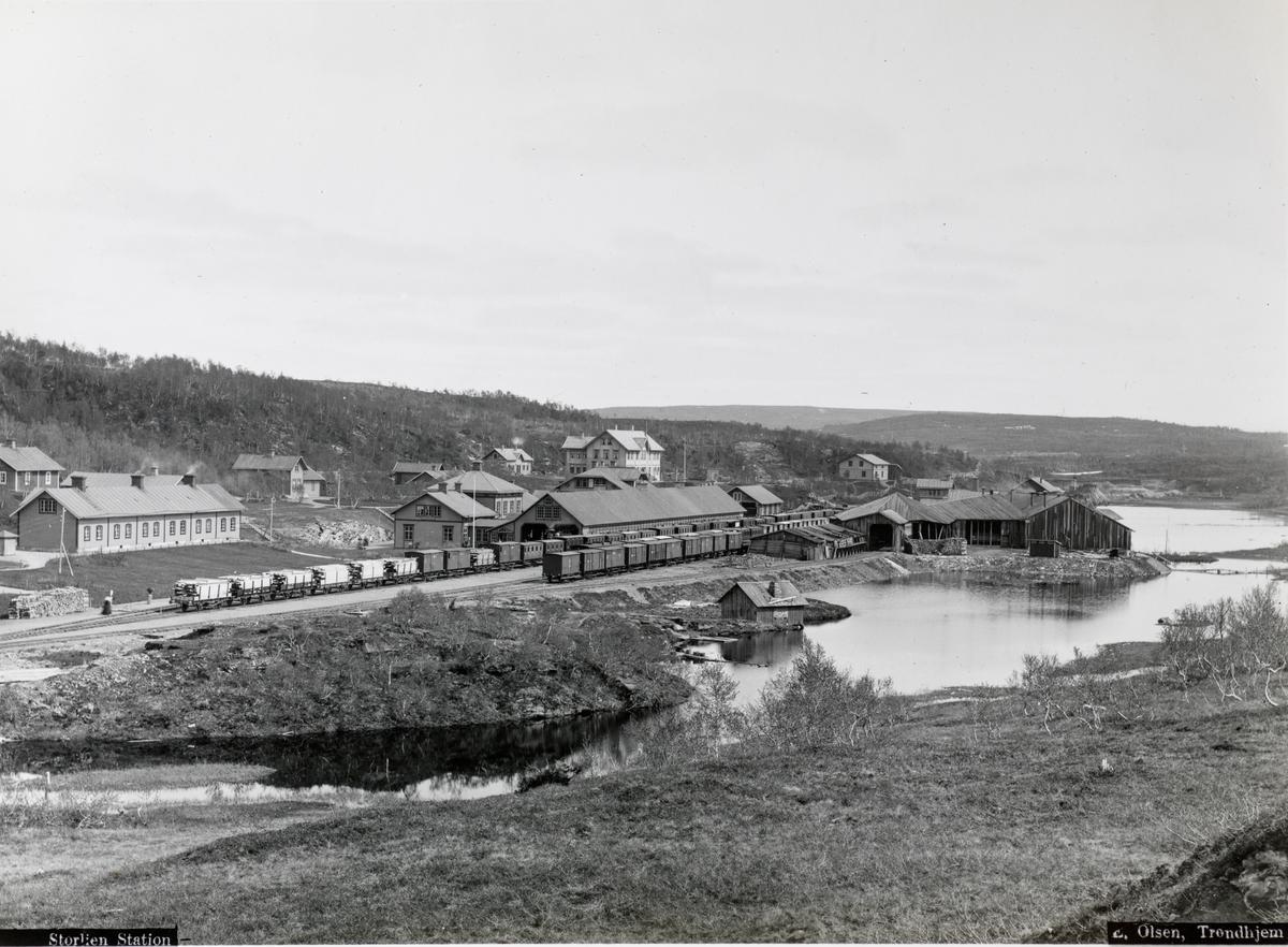 Storlien stasjon med et langt tog med mange personvogner og godsvogner lastet med planker.