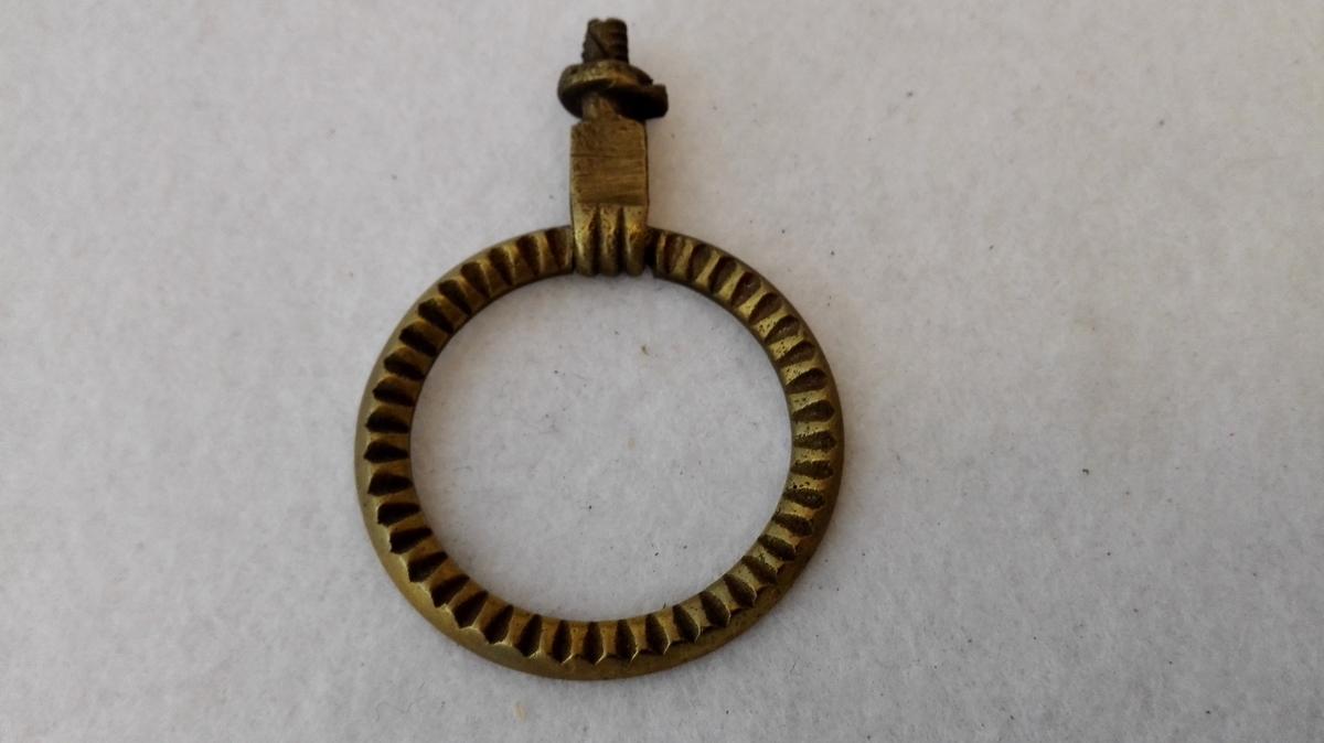 Sirkulær ring med perlestavbord tredd gjennom ei metallhempe festa til skruefeste for tre.
