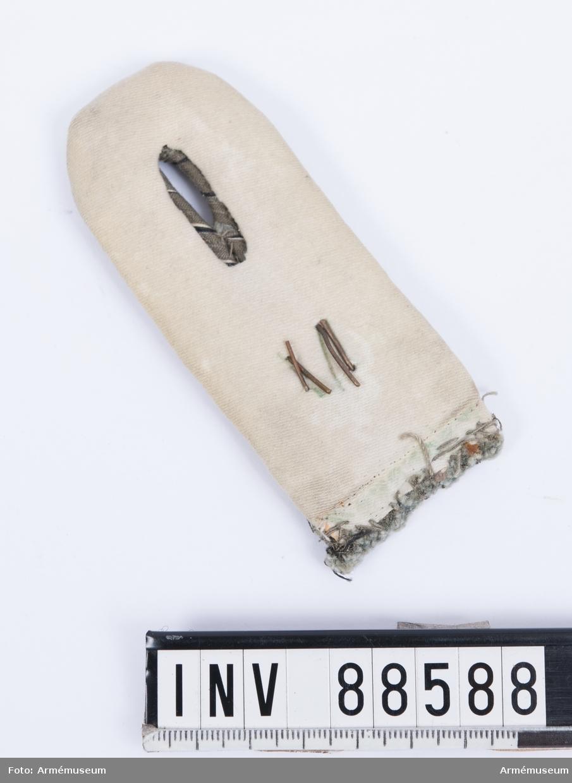 """En axelklaff med fyra vävda snören av grå tråd med svarta och vita inslag (preussens färger) och nummer """"34"""" i gråmålad metall. Kantningen är av vitt kläde. Axelklaffen har sytts fast i axelsömmen och saknar därför slejf på baksidan."""