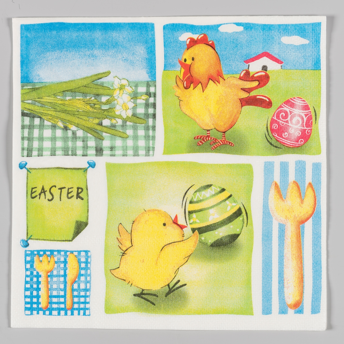 Servietten er delt inn i flere felter med hvert sitt motiv. En kylling og et dekorert rosa påskeegg med et hus i bakgrunnen. En kniv og en gaffel. En kylling og et grønt dekorert påskeegg. En gaffel.