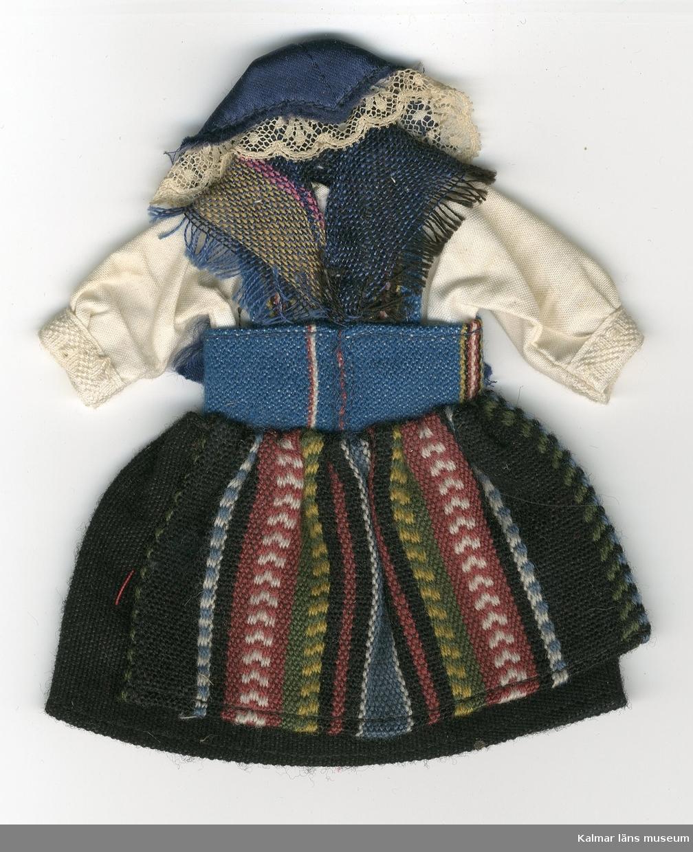 KLM 28082:60. Dockdräkt, dam, av textil, ylle, bomull och siden. Dräkten består av kjol, förkläde, väst, skjorta, schal och huvudbonad. Nationaldräkt från: Umeå, Västerbotten. På baksidan av dräkten ett tygprov fäst.