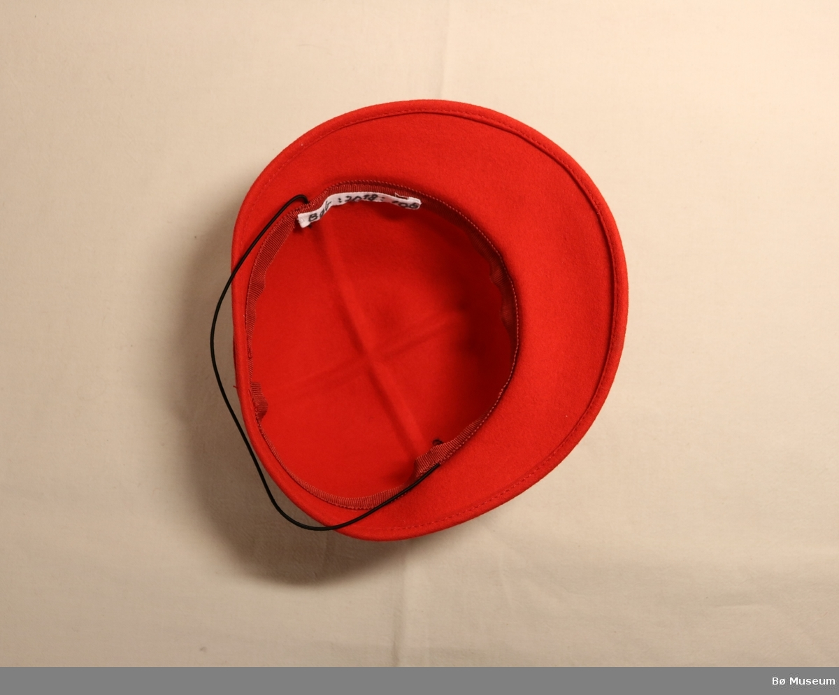 Hatt med brem og sløyfe på framsida. Strikk til å ha under haka.  Ripsband innvendig i pullen, filtband utvendig.