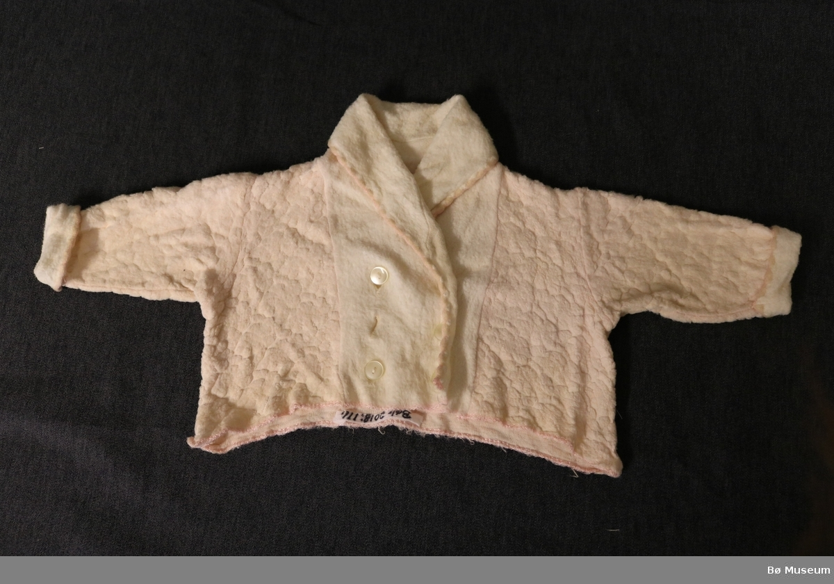 """Dobbeltspent jakke med seks knappehol og """"sjalskrage"""". Krage og ermer har vrangsaumen ut og skal brettast opp. Jakka manglar ein knapp og langs kantane er den overkasta med rosa kunstsilketråd."""
