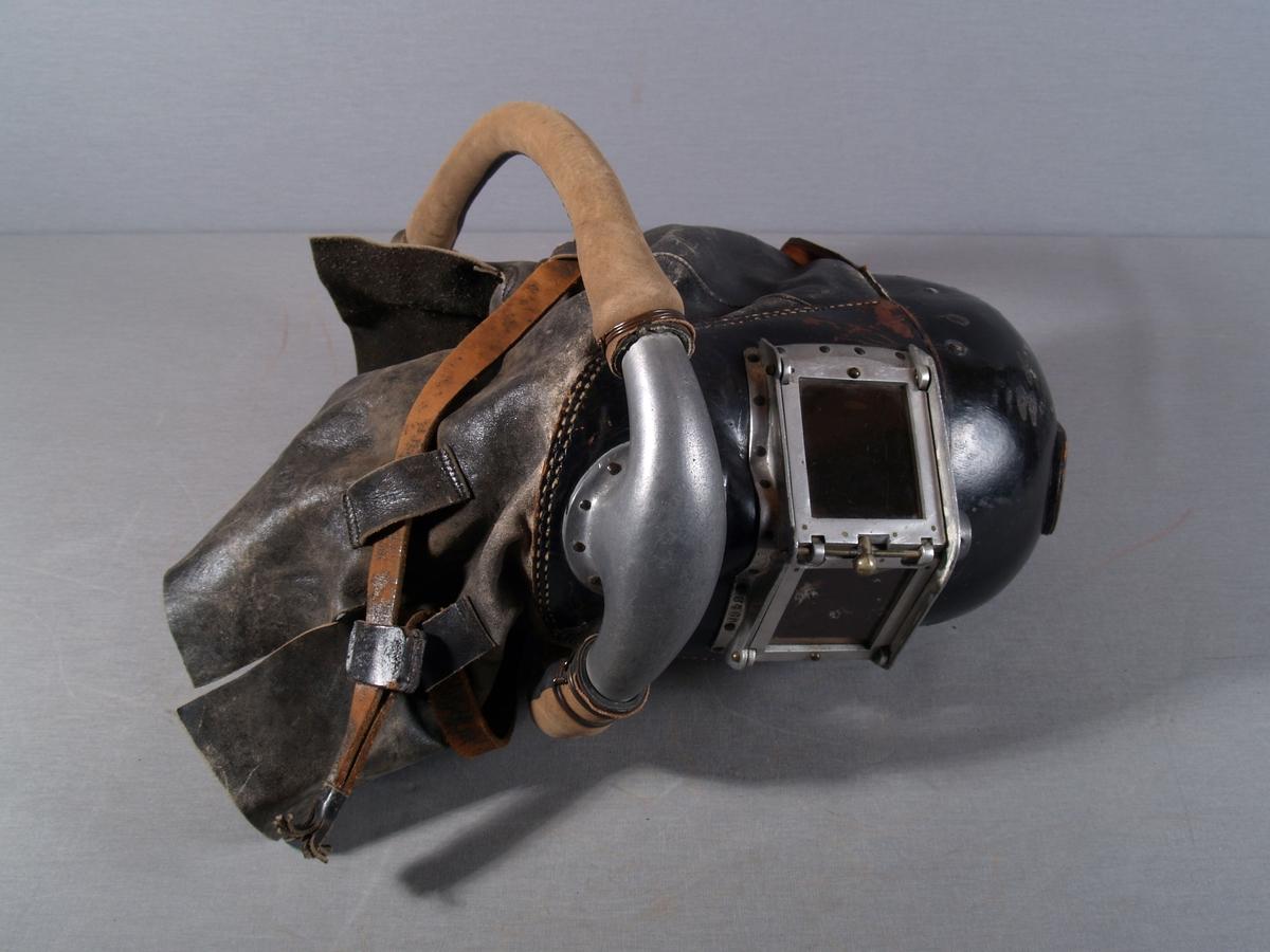 Røykdykkerhjelm i lær med todelt glass i fronten, slanger for lufttilførsel på hver side av hjelmen møtes i et metall munnstykke i front. Lær skjold/krage rundt hele hjelmen med lærrem for å holde lærkragen sammen.