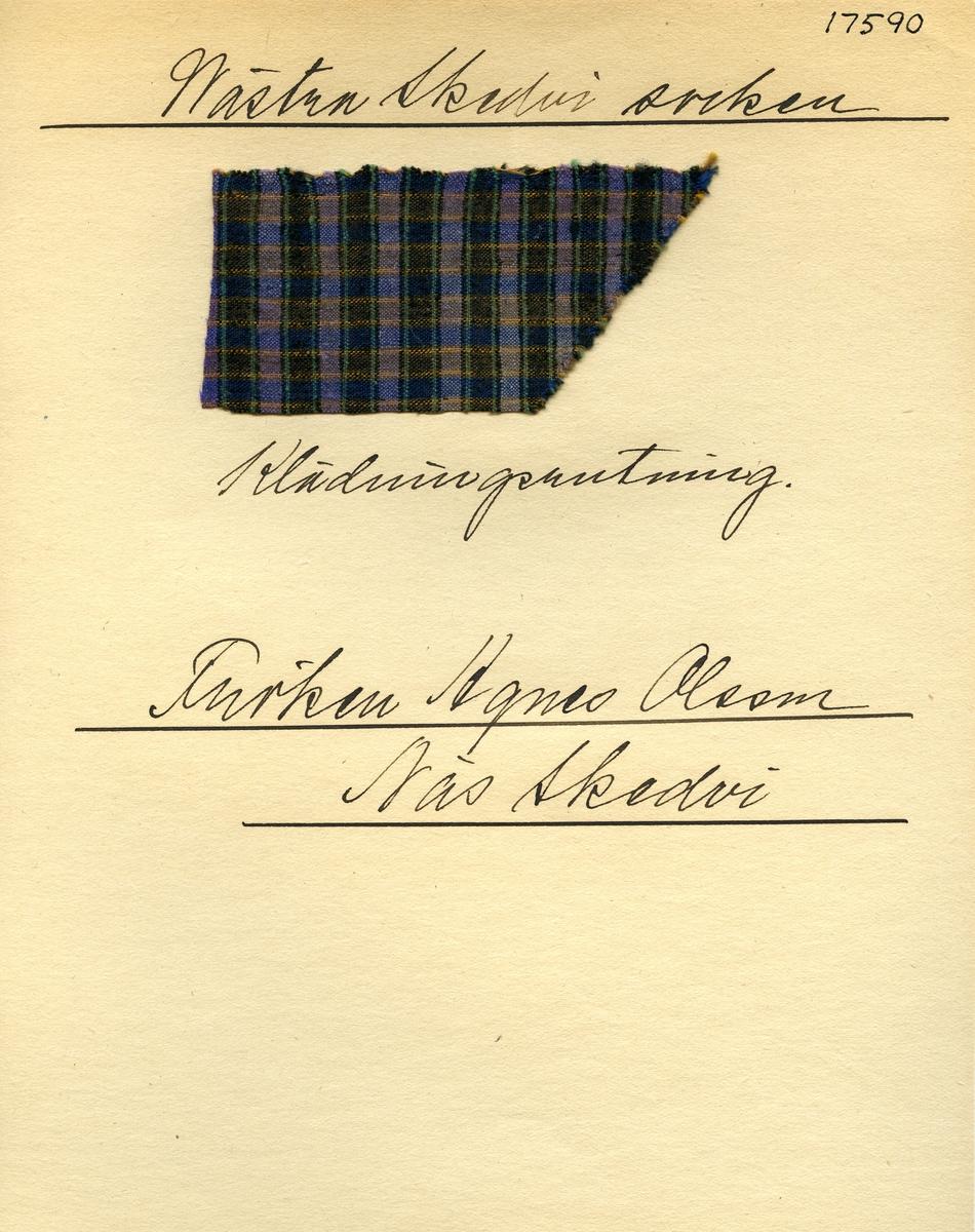 Anmärkningar: Vävnadsprov Olga Anderzons samling. Klänningsrutning, Fröken Agnes Olsson, Näs Skedvi Västra Skedvi sn. Vävprov av halvylle i tuskaft, rutigt. Varpen av bmull och inslaget av ull är lika randade, men i olika färger. Varpen har svarta och gröna ränder på lila botten. Inslaget har gula och bruna ränder på blå botten. L. 470 460 Br. 770 950
