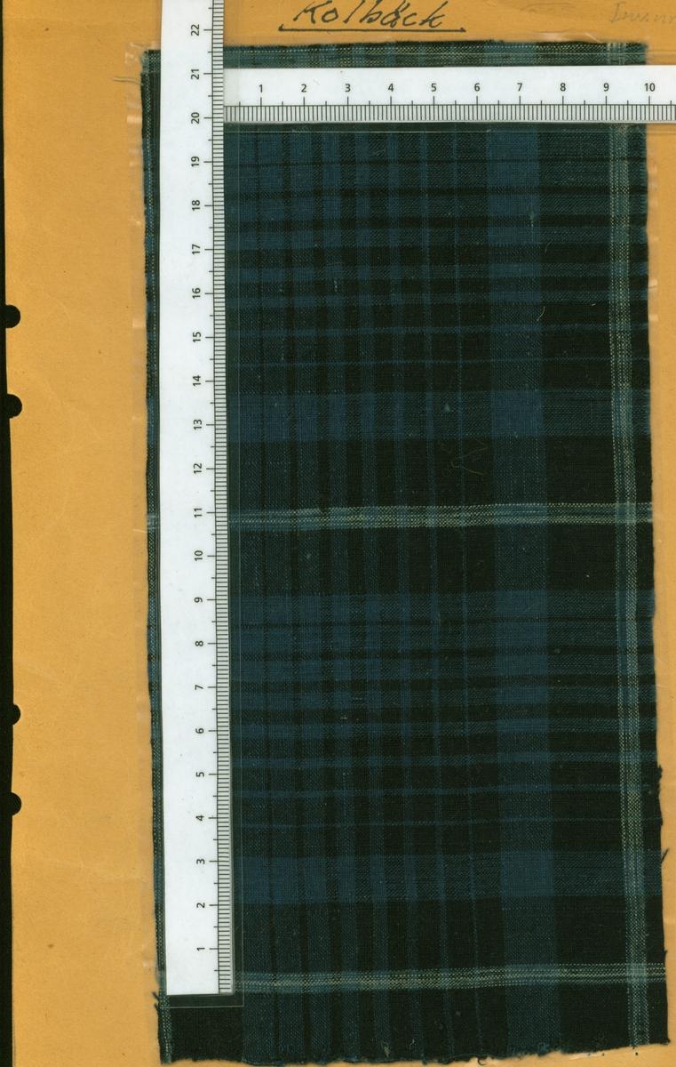 Anmärkningar: Vävprov av bomull i tuskaft, rutigt. Varp och inslag är randade lika i svart, blått och vitt. Ursprungligen ägd av fr Angneta Jansson, Yllesta, Kolbäcks sn. Insamlad och skänkt till museet av Olga Anderzon, Västra Bergsg. 8, Västerås.