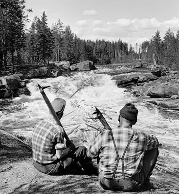 Bildet viser to tømmerfløtere i 1969 ved et av Flisfallene i elva Flisa, Hedmark