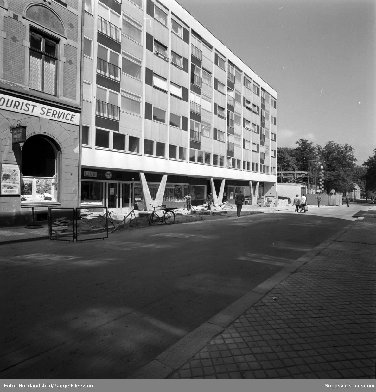 Nybygge vid Kyrkogatan 4-6 är klart. I gatuplan SMC livsmedelsbutik. Exteriörbilder samt en interiör med en kvinna i ett kök.