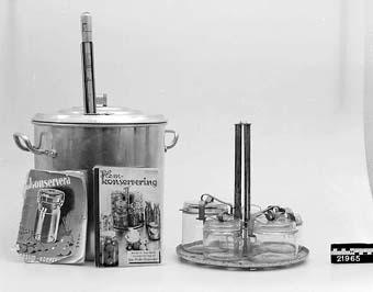 Anmärkningar: Konserveringsapparat bestående av en stor kastrull av aluminium med lock, insats av galvaniserad plåt, nu rostig, 5 glasburkar med lock och klammer. I kastrullens lock en löstagbar termometer. Med apparaten följer 2 st böcker om konservering. Tillverkad vid Skultuna bruk. Inköpt 1922 på Skultuna och gavs som 50 - årsgåva till Hilma Sofia Jacobsson, Västerås, mor till givaren Annna Greta Avelin.