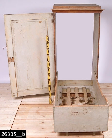 """Anmärkningar: Skåpsäng, 1800-tal.  Spegelförsedd dörr med ett skuret ornament och en järnhasp. Invändigt finns en säng som går att fälla ned (bild 26335__b). Sängen är 1620 mm lång. På skåpets ena kant finns påskriften """"Eva"""" i blyerts. H:1500 Br:695 Dj:600  Hela skåpet är brunmålat. Invändigt är det gråmålat.  Invnr. är dubbelmärkt, se invnr. 15892.  Tillstånd: Ett flertal lister är lösa och två saknas. Bakstycket är löst. Lås och nyckel saknas."""