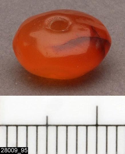 Anmärkningar: Badelunda sn, Tuna undersökt 1952-1953 Pärla, från båtgrav daterad till yngre järnålder, 850 e.Kr. (Vikingatid)  Pärla av glas, från grav 75 (fyndnr 95), 1 st, rödbrun av karneol. Diam 11 mm Tjl 6 mm Utställd Forntid 2014  Pärlorna från grav 75 har omregistrerats av Access-projektet 2007 och då registrerats på enskilda poster under sitt ursprungliga (från rapporten) fyndnummer.  Litteratur Nylén, E. & Schönbäck, B. 1994. Tuna i Badelunda. Guld kvinnor båtar I. Västerås kulturnämnds skriftserie 27. Västerås. s 44ff. Nylén, E. & Schönbäck, B. 1994. Tuna i Badelunda. Guld kvinnor båtar II. Västerås kulturnämnds skriftserie 30. Västerås. s 112 ff, 150ff, 200.  Fotograferad teckning negnr A-7422