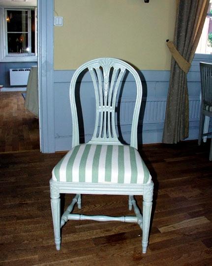 Anmärkningar: Gustaviansk stol, omkring 1790. Skuren vetekärve i överstycket, genombruten ryggbricka. Kannelerad spjälad rygg (fem spjälor). Rundat överstycke med kälningar. Kälad sarg. Rosettanfanger i framsargens hörn. Svarvade ben, de främre med kannelyrer. Svarvat H-kryss mellan benen. Löst ilagd stoppad sits.