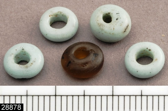 Anmärkningar: Badelunda sn, Tuna undersökt 1952-1953 Pärla, från båtgrav daterad till yngre järnålder, 850 e.Kr. (Vikingatid)  Pärlor av glas, från grav 75. 4 st små vita och en liten brun genomsiktig. Diam ca 8 mm Utställd Forntid 2014  Tidigare registrerade med de övriga små pärlorna från grav 75 som pärlband under invnr 28008. Vid genomgång av accessprojektet har pärlorna från grav 75 i möjligaste mån återförts till det ursprungliga inventarienumret och fyndnumren från rapporten. På pärlorna som registrerats under detta invnr har det ursprungliga fyndnumret försvunnit (nötts bort). Dessa pärlor hör troligen till  något av fyndnumren 20, 75 eller 111 från grav 75.  Litteratur Nylén, E. & Schönbäck, B. 1994. Tuna i Badelunda. Guld kvinnor båtar I. Västerås kulturnämnds skriftserie 27. Västerås. s 44ff. Nylén, E. & Schönbäck, B. 1994. Tuna i Badelunda. Guld kvinnor båtar II. Västerås kulturnämnds skriftserie 30. Västerås. s 112 ff, 150ff, 200.  Fotograferad teckning negnr A-7422