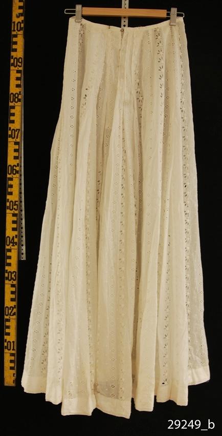 Anmärkningar: Irsta sn Geddeholm Använd troligen av Elisabeth Lewenhaupt född 1888 död 1982. Saknar skriven skylt.  Kjol av vit bomullsbatist med brodyr, med sydda vertikala stråveck. Knäpps med åtta hakar med hyskor mitt bak.
