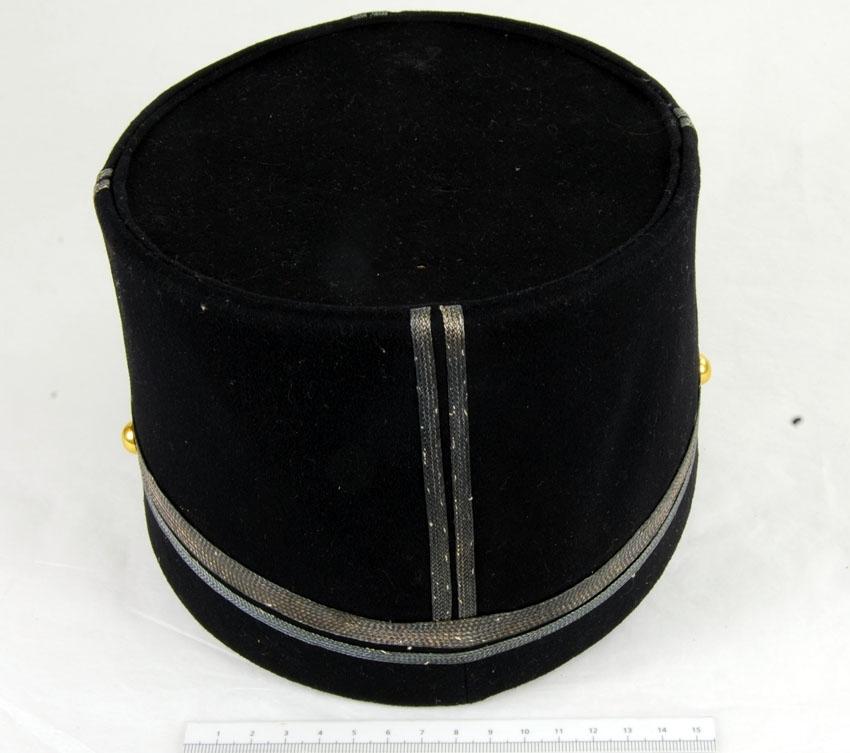 Anmärkningar: Irsta sn Geddeholm Har tilhört ryttmästare Folke Linton född 1916 död 1996.  Mössa , 1 st, av mörkblått kläde, samma som livplagget, med skärm och rem av svartlackerat läder. Två st stolpar av 5 mm galoner i guld. En smal galon (5 mm) runt kullen = gradbeteckning för underlöjtnant. Kokard m/1865 av gult plisserat siden i två lager, med en överklädd pistill. Kupad knapp med blå emalj och tre kronor i guld. Kupad knapp, modell mindre, på vardera sidan. Guldfärgat spänne i mössremmen (13 x 16 mm). Beigt linnefoder. Märkt inuti på kanten av kullen Örebro Nya hatt och mössmagasin C. J. Hellströms.