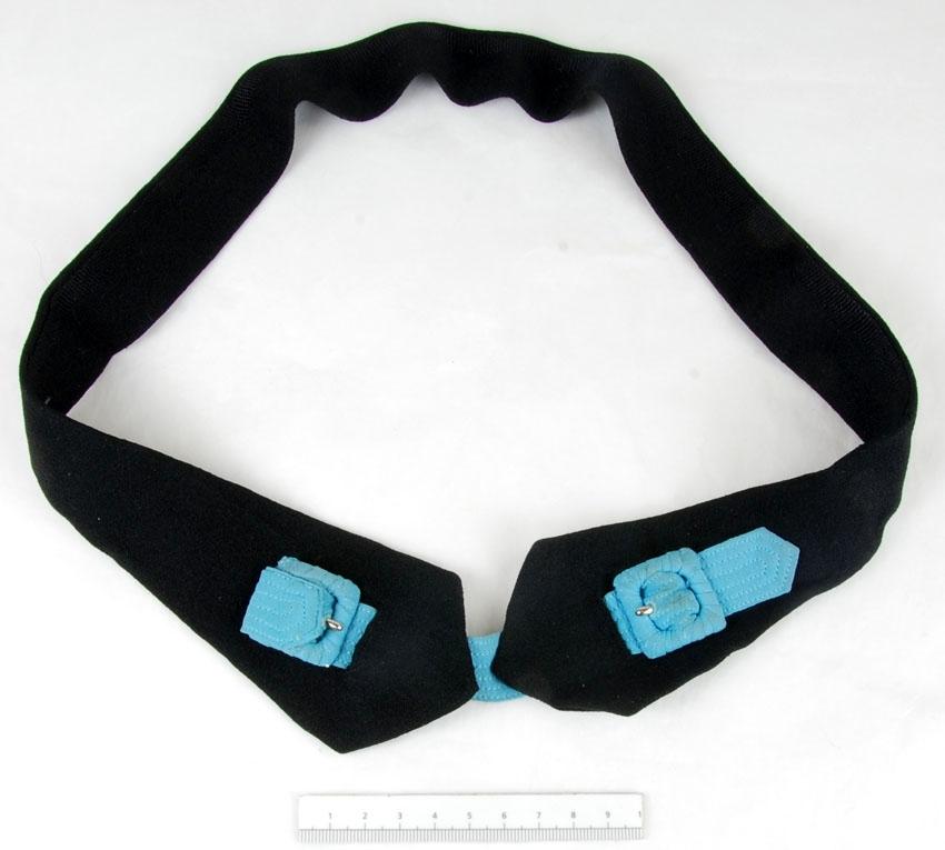 Anmärkningar: Irsta sn Geddeholm  Skärp, 1 st, av svart crepat  karftigt tyg att bäras runt midjan. Ändarna breddare än övriga delen av skärpet och avslutas i > < - form. De fästs ihop med ett blågrönt smalt band vars längd regleras med en liten klädd sölja i vardera änden.