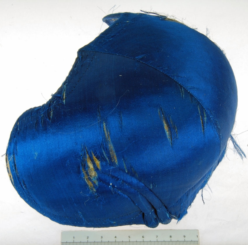Anmärkningar: Irsta sn Geddeholm  Bindmössa, 1 st, av blått siden. Inuti klädd med naturfärgat linne. Mössan saknar stycke. Slitet sidentyg. Tillhör folkdräkt. Förvaras i hög oval brun låda med lock. (Bindmössa, liten, styvad, rundkullig mössa, vanligen sidenklädd och broderad och ofta prydd med rosett baktill eller runt kullen. Den bärs högt uppe på kvinnans huvud och kompletteras av ett stärkt, spetsprytt s.k. stycke av lin. Källa NE)