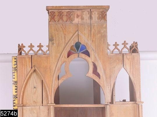 Anmärkningar: Skrivbord, tredelat, nygotik, 1800-talets mitt.  Överdel (omfattande två delar): Trappstegsformad överdel med spetsformigt gallerverk och kors. Skurna axliknande ornament längst upp (bild 5274__b). Öppning i mitten med avslutande spetsvinkligt masverk med från vänster röda, gula, gröna, blåa och lila blyinfattade glasinlägg (bild 5274__b). Tre hyllplan i öppningen (ett saknas). Öppningen flankeras av spetsvinkliga fyllningar med knippepelare och kapitäl.  På vänster fyllning finns två krokar i mässing.Två draglådor nederst med knoppar av elfenben. Skåp på sidorna med nyckelskylt av mässing och invändigt vardera ett hyllplan. H:1920 Br:890 Dj:430  Skrivbordsdel: Framskjutande skrivbordsskiva. Tre draglådor med nyckelskyltar i mässing. Skrivbordsdelen vilar på två kolonner. Bakom kolonnerna finns en valvformad öppning som flankeras av två pilastrar. Skåp på sidorna med nyckelskylt av mässing och invändigt vardera ett hyllplan. H:805 Br:930 Dj:750  Skåpet är helt fanérat i alm med blindträ av furu.  Tillstånd: Axornament, lister, glas, kapitäl, delar av bakstycket och inlägg i höger spetsbåge saknas på den översta delen. I öppningen saknas ett hyllplan. Fanérbitar saknas och är lösa på hela skåpet (bild 5274__c). Lösa delar ligger i vänster låda på överdelen.  Historik: Tillhört Landshövding Wersäll, Västerås. Köpt å auktionskammaren 1926.