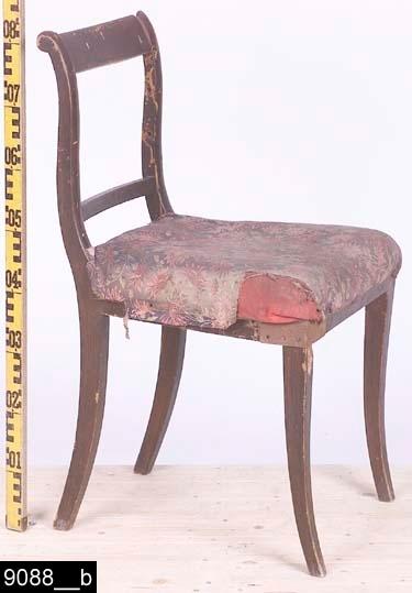 Anmärkningar: Stol, Karl Johan modell, 1800-tal.  Svagt konvext överstycke. S-svängda bakstolpar (bild 9088__b). Genombruten rygg med en ryggslå. Stoppad sits med blommigt tyg. Fyra ben som samtliga är utåtsvängda från stolen (bild 9088__b). H:825 Br:475 Dj:485  Hela stolen är av ljust lövträ, utom fyra förstärkningar under sitsen som är av furu. Äldre rött tyg skymtar igenom det blommiga tyget.  Tillstånd: Stolen är maskstungen. En ryggbricka eller ryggslå saknas. Vänster framben är skadat och utvändigt försett med en vinkelformig förstärkning i järn. Samtliga sargar har undertill halvcentimeter stora runda hål, sannolikt efter gamla nitar som fäst ett nu borttaget tygöverdrag på sitsen (bild 9088__c).  Historik: Gåva fr. Olga Anderzon, Västerås, 1930-tal. Enligt liggaren ska inventarienumret innefatta två stolar. Enligt kortkatalogen finns det endast en. Den saknade stolen finns ej i 2003 års inventeringsförteckning över Vallby.