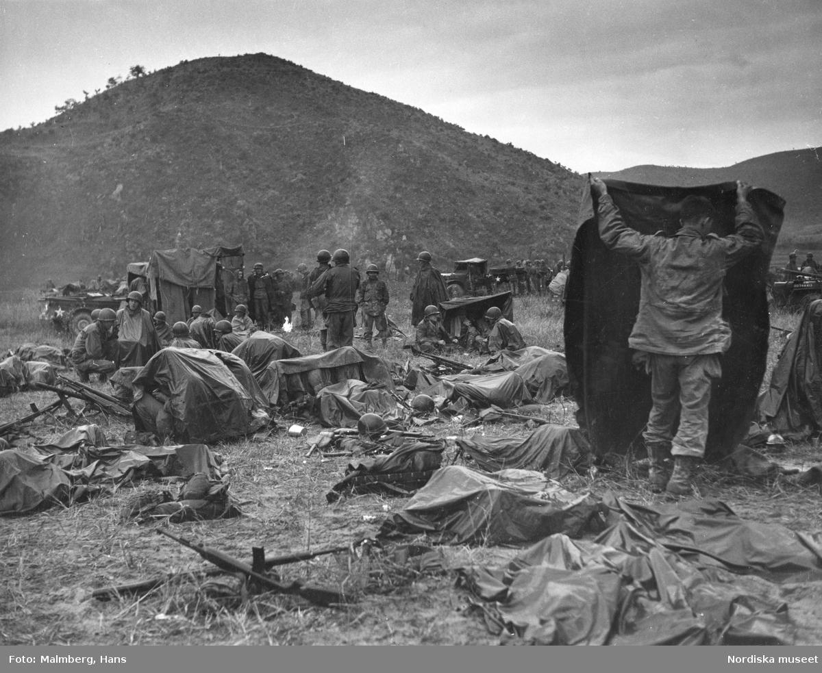 Koreakriget. Amerikanska soldater vilar ut på ett fält.