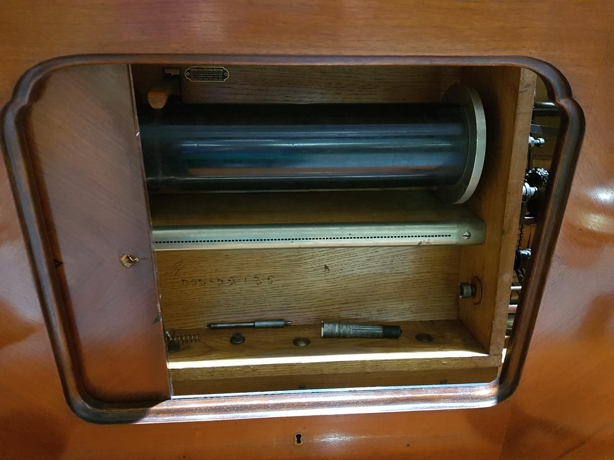 Elektrisk piano i finért mahogny. To lampetter i art deco stil med kløverformet intarsia bak. I midten er det en låsbar luke med oval dekor i intarsia. På stolpene i front er det perlerad i ibenholt. Notestativ under lokket. Omfang AAA-a4