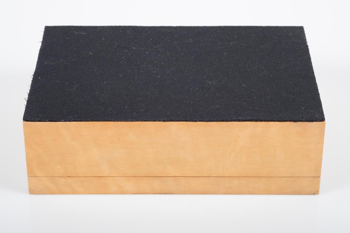 Enkelt treskrin med svart ullstoff på undersiden, laget av en gammel gardistuniform. Laget på Grini av fange 10121 Gudmund Johan Bjørnstad til sin kone.