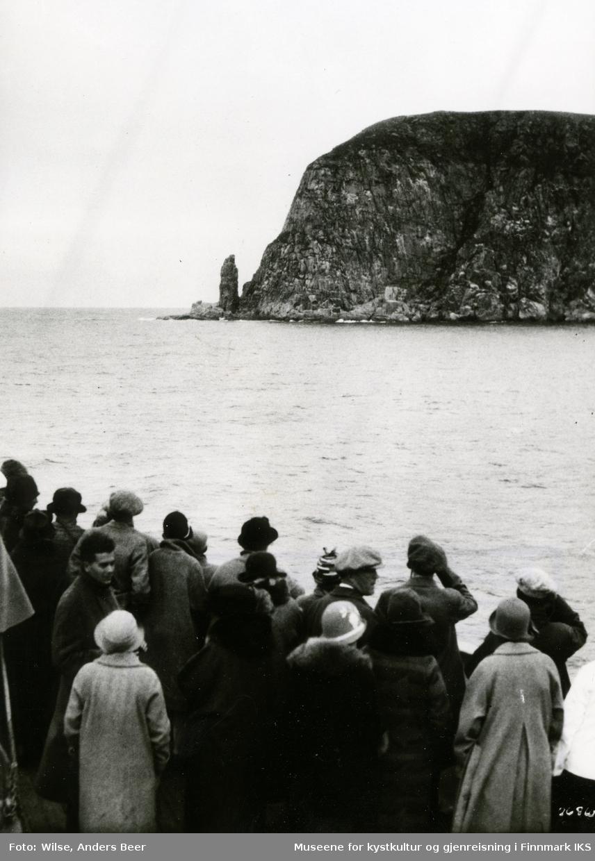 """Turister på vei til Nordkapp med D/S """"Stavangerfjord"""" se på fuglebjerget Hjelmsøystauren. Sommeren 1925. (Originalnegativet eies av Norsk Folkemuseum, W 26910)"""