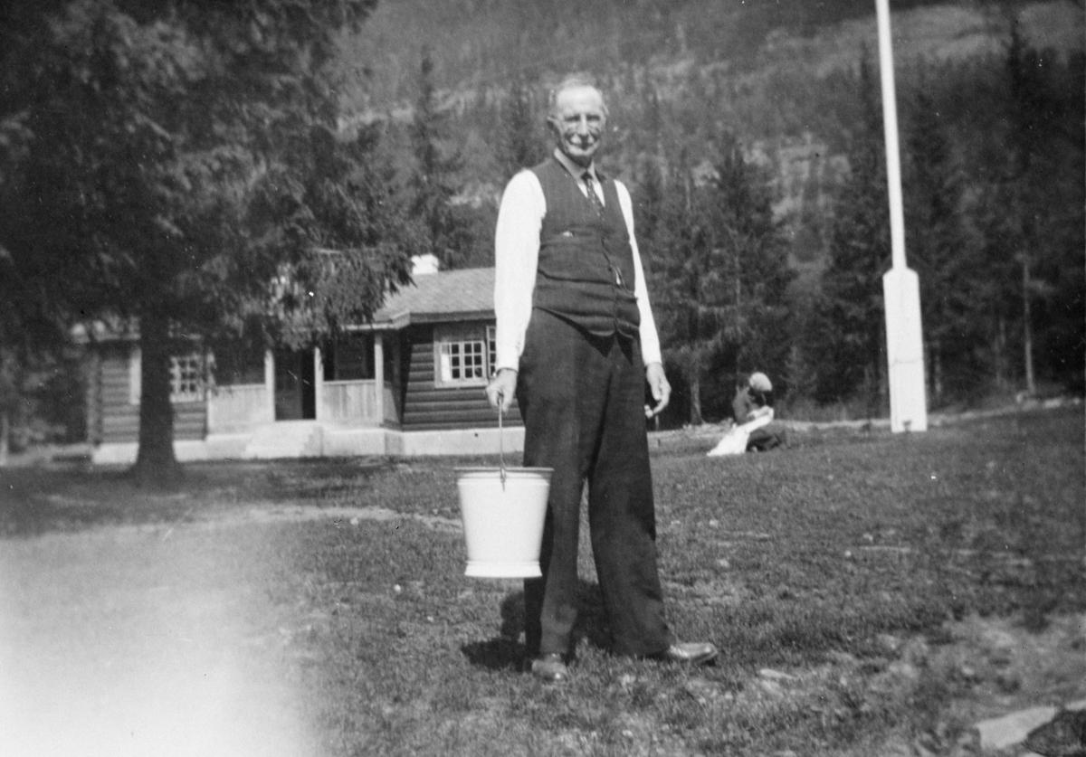 Portrett av mann, som bærer en bøtte