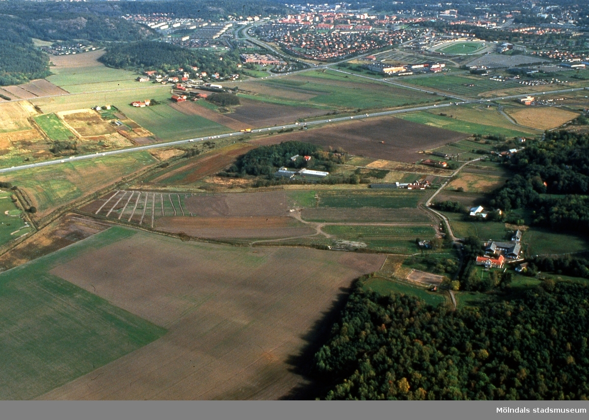Vy från väster mot Fässbergsdalen, Mölndal, i september 1989. I förgrunden ses Lunnagården i Balltorp. I mitten ses trafik på Söderleden. I bakgrunden ses Fässberg samt de mer centrala delarna av Mölndal. Flygfotografi. Duplikat från kommunens foto. FD 5:26.
