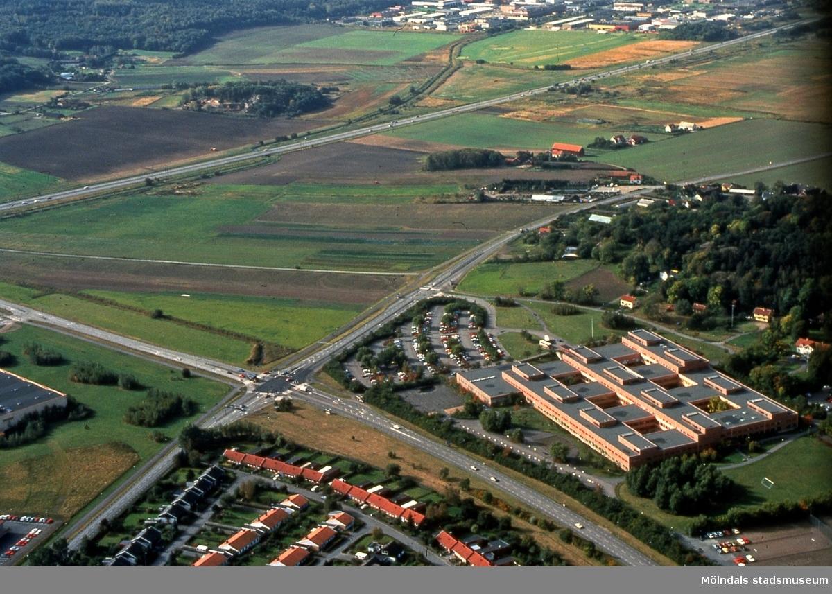 Fässbergsdalen, Mölndal, i september 1989. I förgrunden ses bostadsbebyggelse på Solängen samt Lärarhögskolan. I mitten ses trafik på Söderleden. I bakgrunden ses Balltorp. Flygfotografi. Duplikat från kommunens foto. FD 5:30.