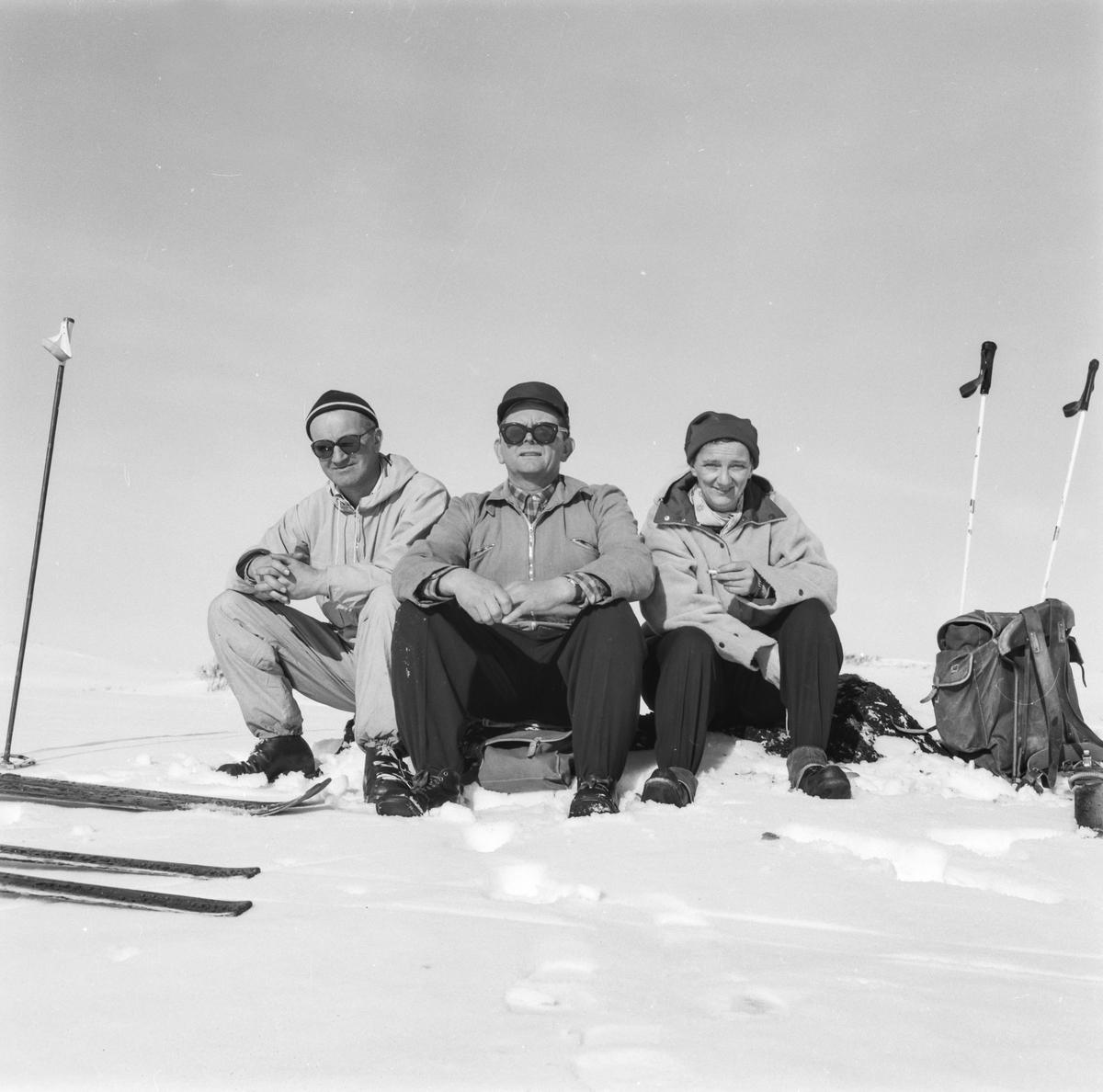 Vinter og snø to menn og ei kvinne på skitur, anorakkar, strekkbukser, beksaumsko, solbriller, ski og stavar, skyggehue, Kongsberghue, panneband, ryggsekk, ransel,