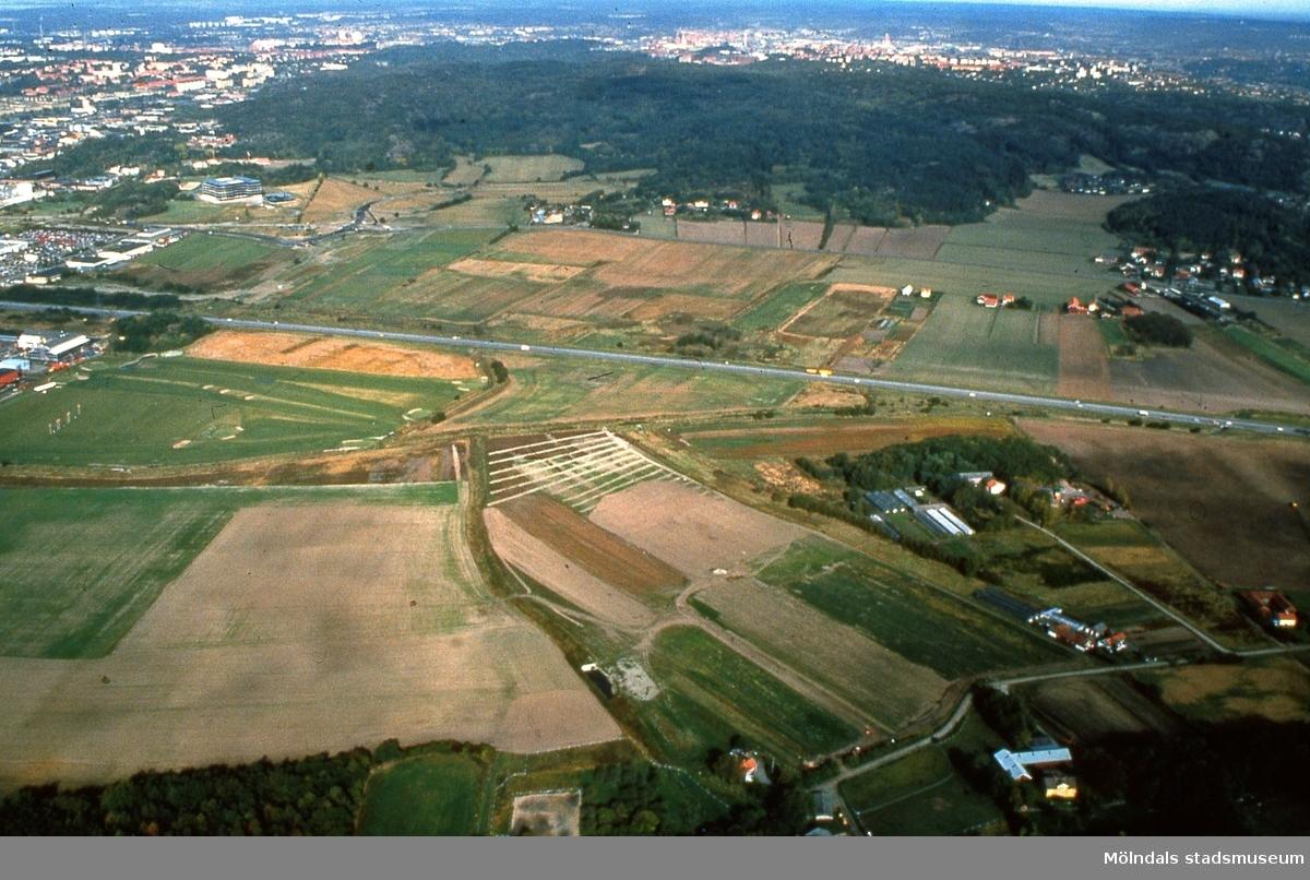 Flygfotografi över del av Fässbergsdalen, Mölndal, i september 1989. I förgrunden ses Lunnagården i Balltorp. I mitten ses trafik på Söderleden. I bakgrunden ses Eklanda och Fässberg. Duplikat från kommunens foto.