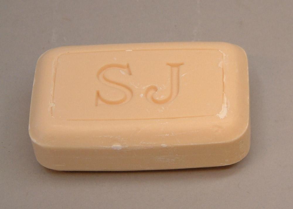 Två stycken gulvita rektangulär tvålar. En nedsänkt rektangel ovanpå med initialerna SJ inpressade.