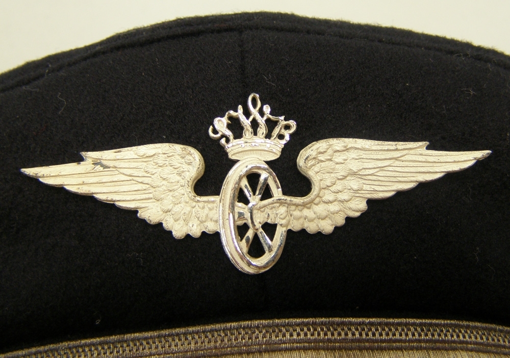 Oanvänd skärmmössa av mörkblått kläde med jaquardvävt rött mössband, samt 13 mm silvergalon och vinghjul krönt av SWB-monogram. Nationalkokard av metall, silverträns och silverknappar.